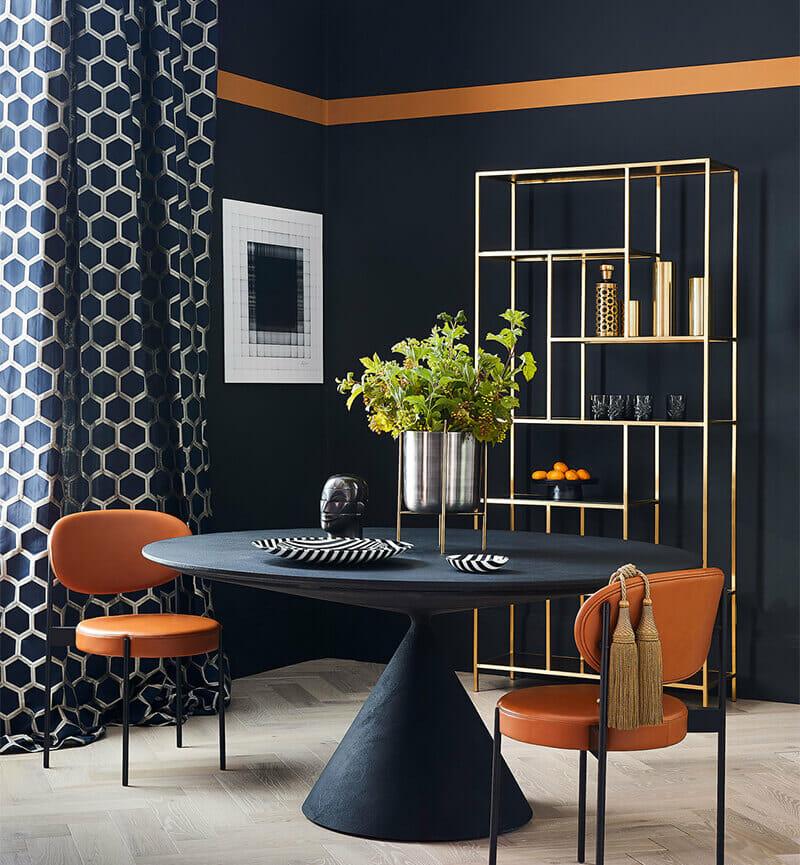hình ảnh một căn phòng với tường và bàn màu xanh than, rèm cửa họa tiết hình học, ghế ngồi bọc da màu vàng da bò