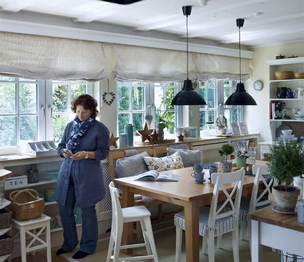 hình ảnh người phụ nữ luống tuổi đứng cạnh bàn ăn
