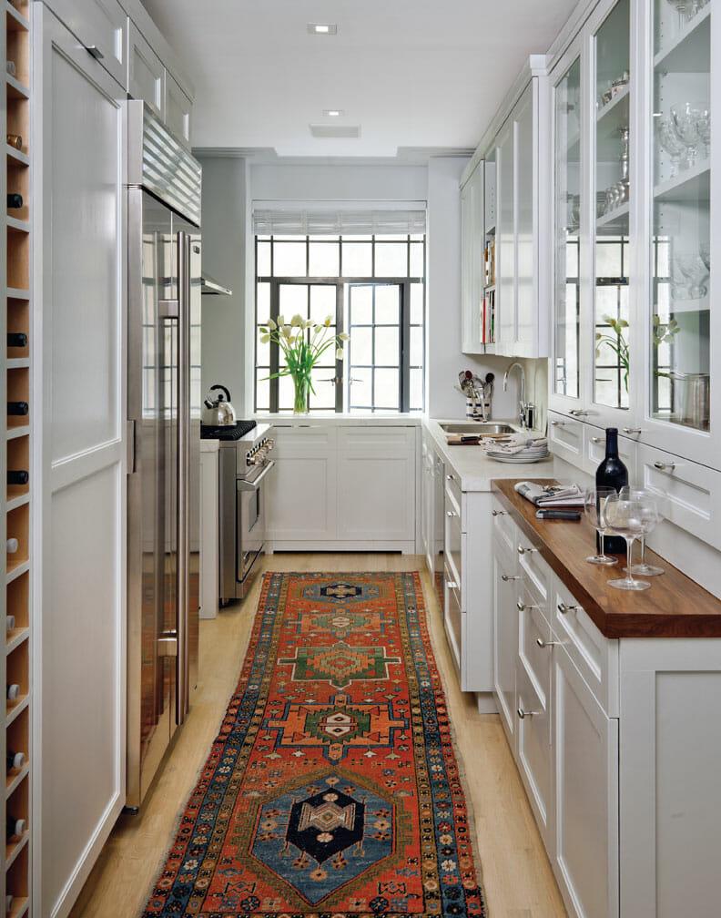 hình ảnh phòng bếp phong cách Art Deco với hệ tủ bếp màu trắng cao kịch trần, thảm trải thổ cẩm màu rực rỡ
