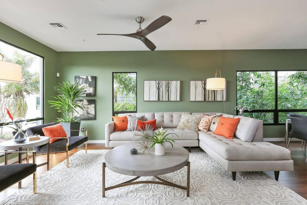 hình ảnh phòng khách màu xanh lá với sofa trắng xám, cửa sổ kính trong suốt, gối tựa màu cam bắt mắt