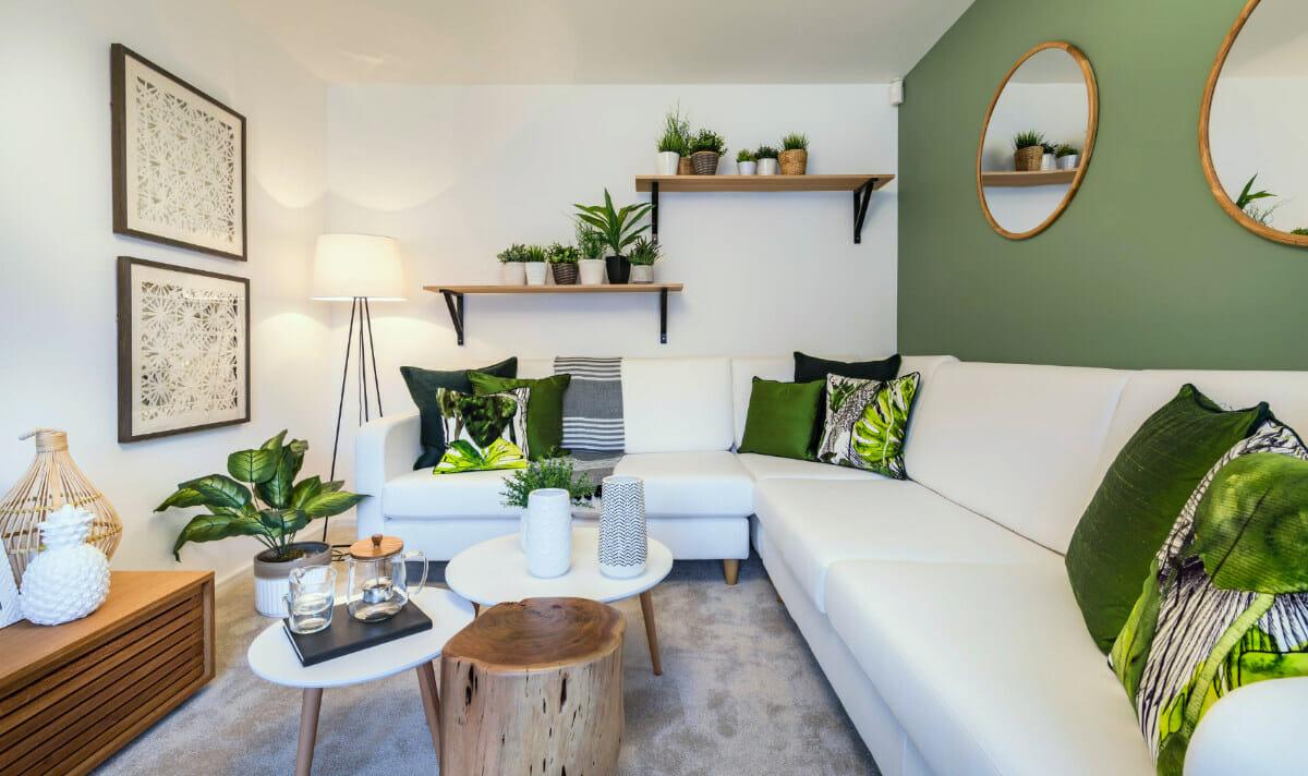 hình ảnh phòng khách được trang trí với tường, gối tựa màu xanh lá, cây xanh tạo điểm nhấn