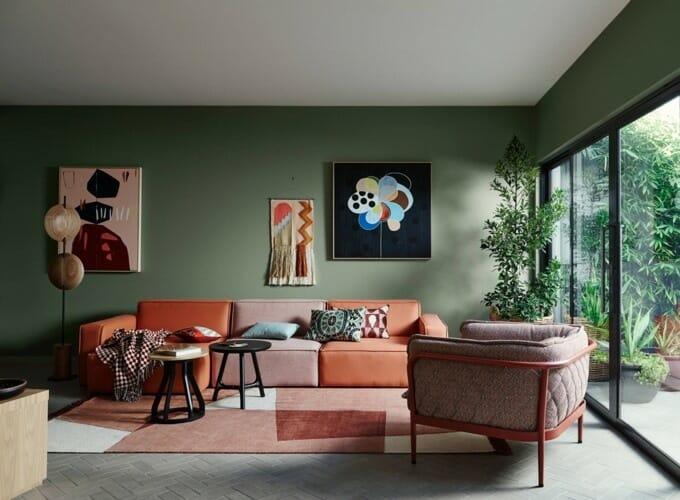 hình ảnh phòng khách hiện đại với tường sơn màu xanh lá trầm, cửa kính trong suốt