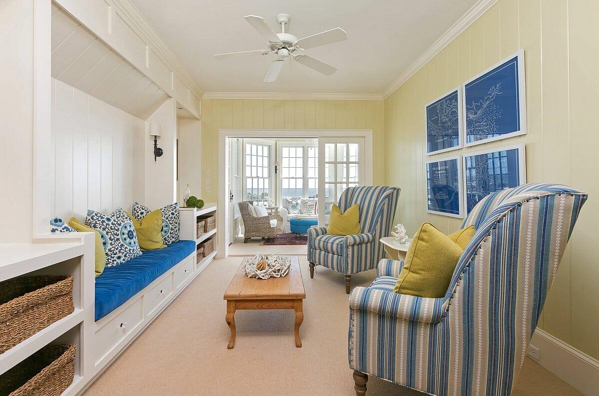 hình ảnh phòng khách phong cách bãi biển với sofa, ghế bành màu xanh dương - trắng, gối tựa màu vàng tạo điểm nhấn