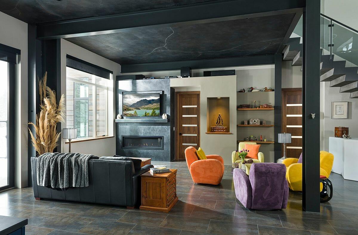 hình ảnh phòng khách ấn tượng với tường sơn màu xám đen, khung cửa sổ kính lớn, ghế bành thư giãn nhiều màu sắc