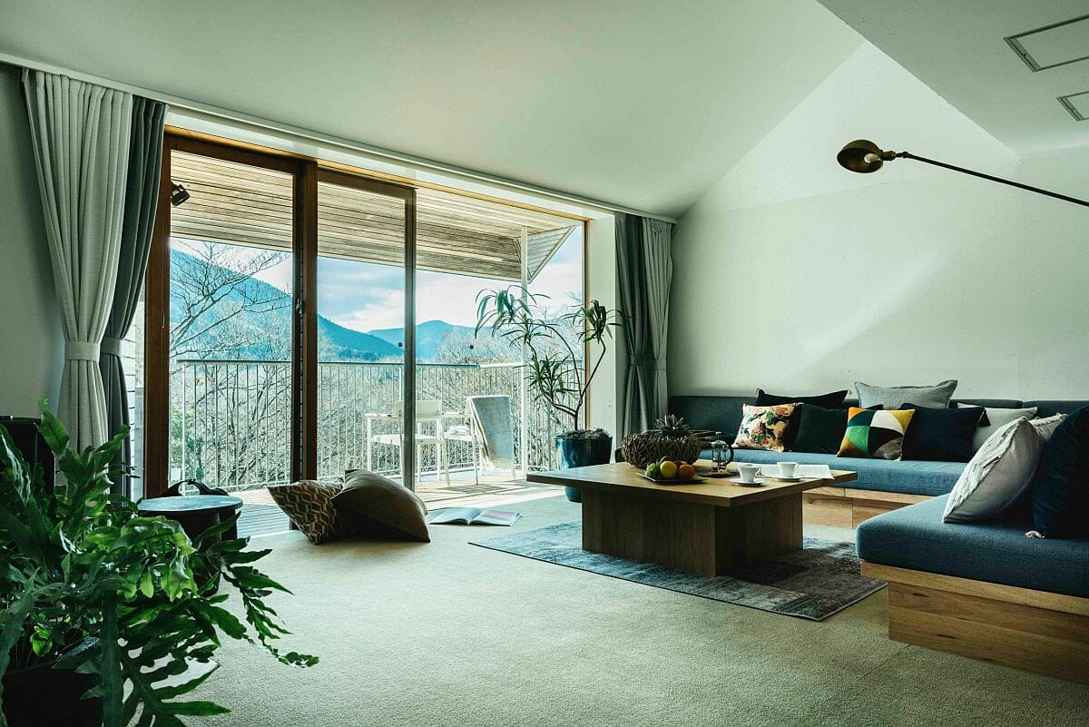 Hình ảnh phòng khách được bài trí với tông màu xanh mint chủ đạo từ tường, rèm cửa, thảm trải