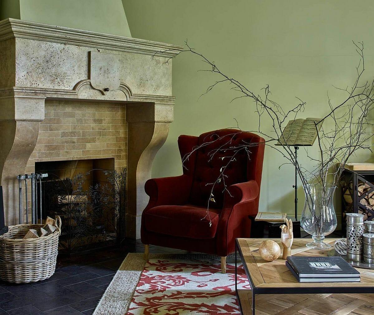 hình ảnh góc phòng khách ấn tượng với ghế bành nhung đỏ nổi bật trên nền tường màu xanh bạc hà
