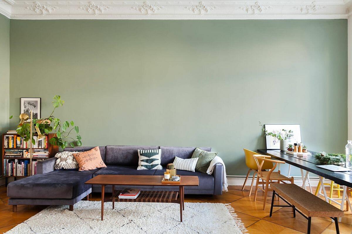 hình ảnh phòng khách với tường sơn màu xanh mint đậm, ghế sofa tím, bàn tà gỗ, thảm trải, cạnh đó là bàn ghế ăn