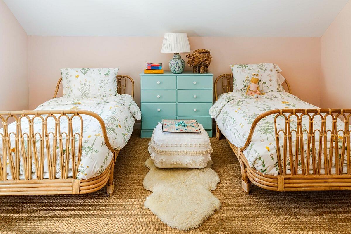 hình ảnh phòng ngủ chung của hai con gái tông màu pastel nhẹ nhàng với giường mây tre đan, tủ ngăn kéo ở giữa màu xanh ngọc, ga gối họa tiết hoa lá
