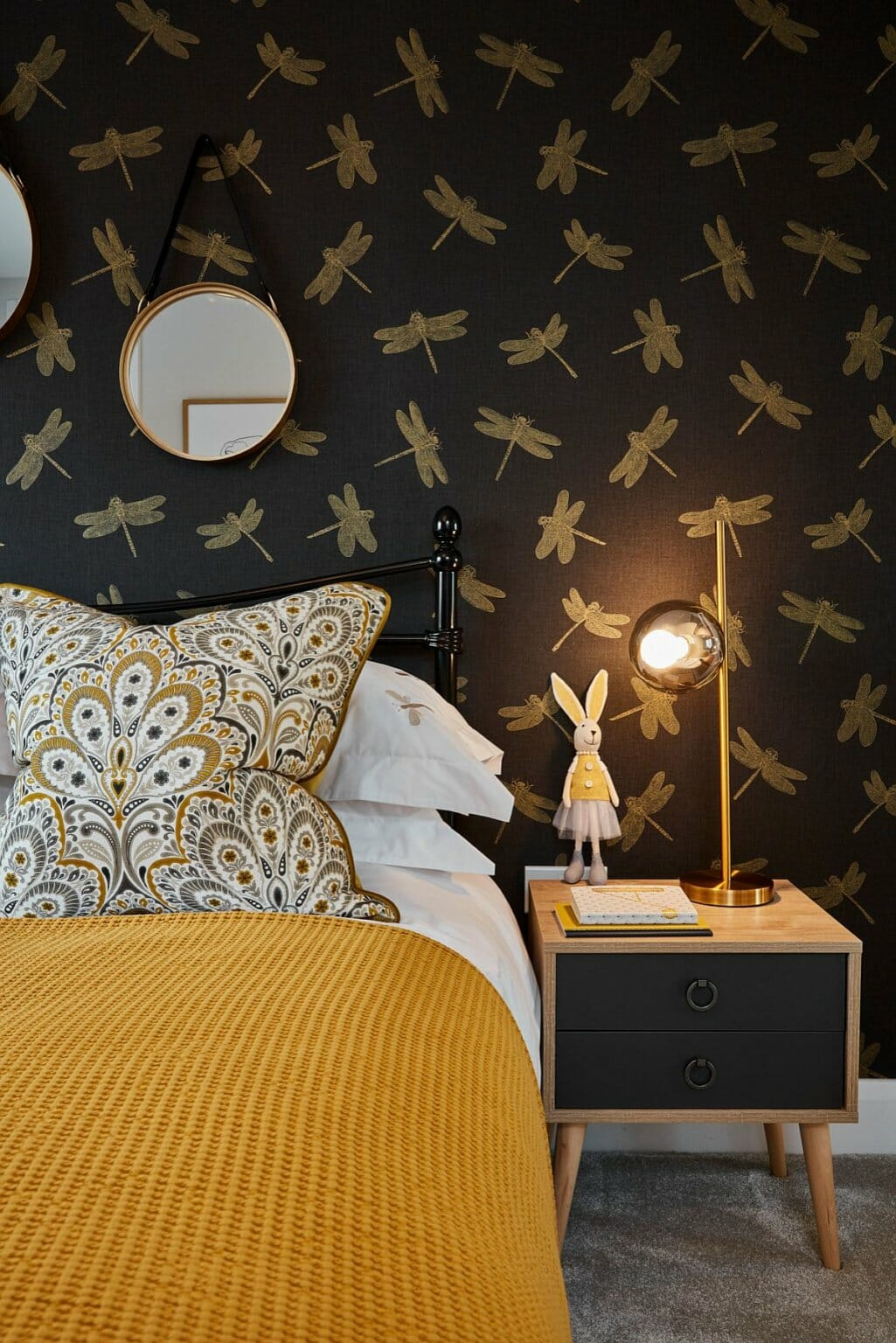 hình ảnh một góc phòng ngủ con gái với giấy dán tường nền đen, họa tiết chuồn chuồn, gối hoa, chăn vàng