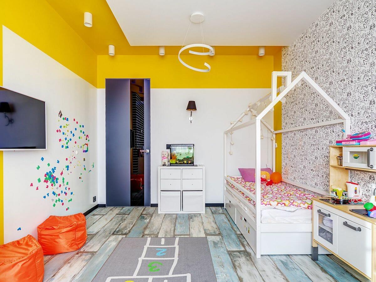 hình ảnh phòng ngủ con gái với giường khung ngôi nhà, màu vàng ấn tượng cho trần và tường, tủ ngăn kéo màu trắng, ghế lười màu cam