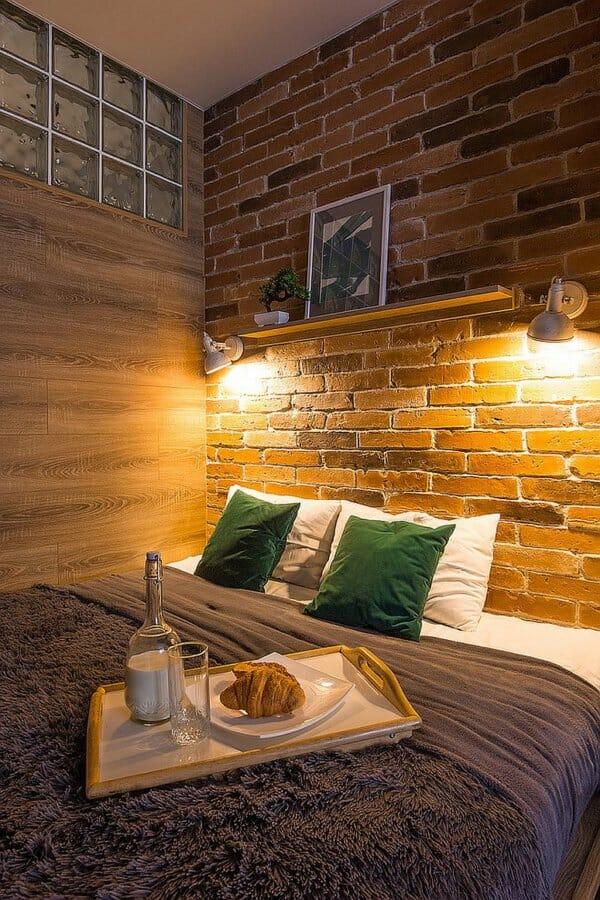 hình ảnh phòng ngủ nhỏ được trang trí với tường gạch đầu giường, đèn chiếu sáng, gối màu xanh lá