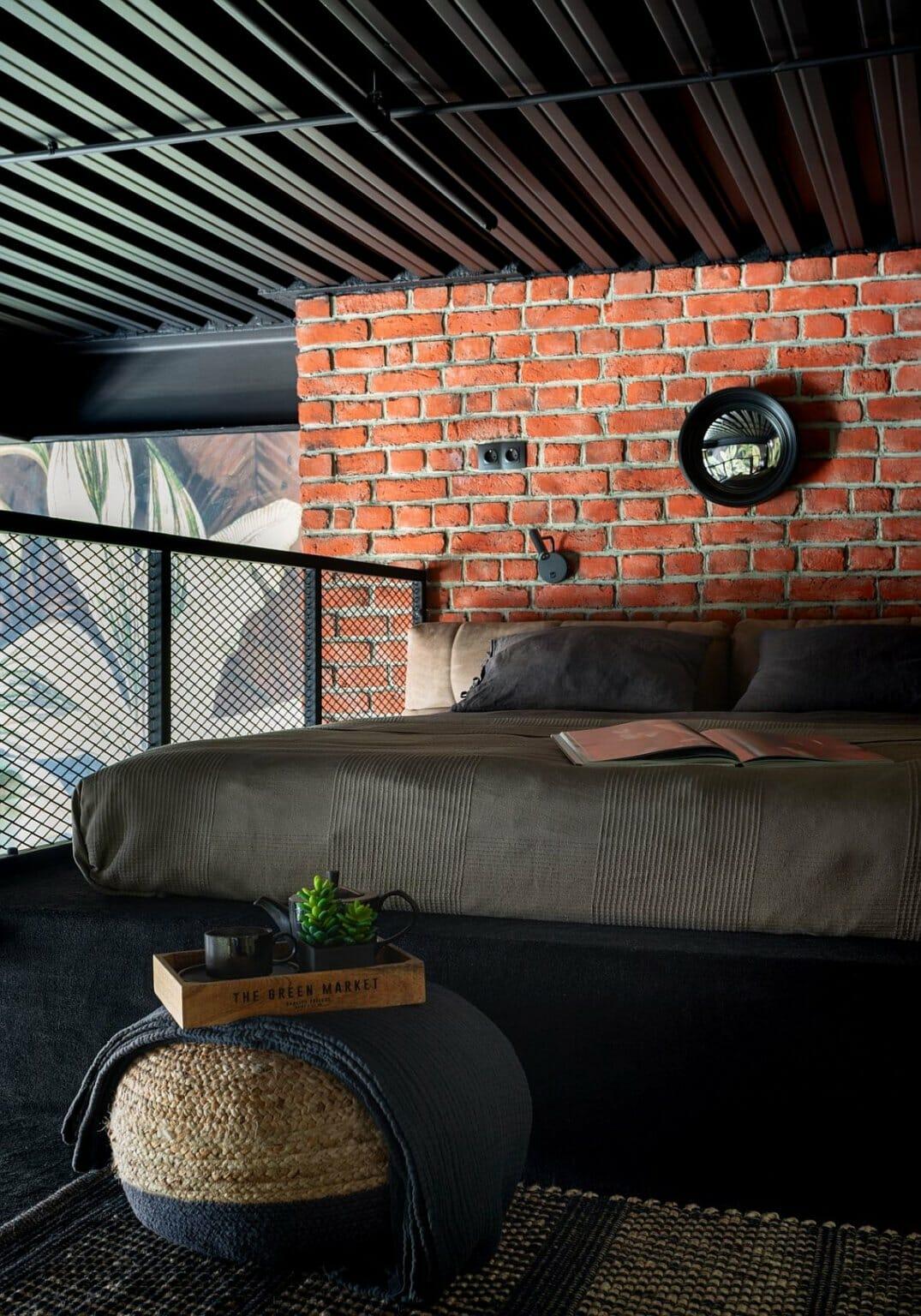 hình ảnh phòng ngủ nhỏ trên gác lửng với lan can lưới kim loại, tường gạch đầu giường