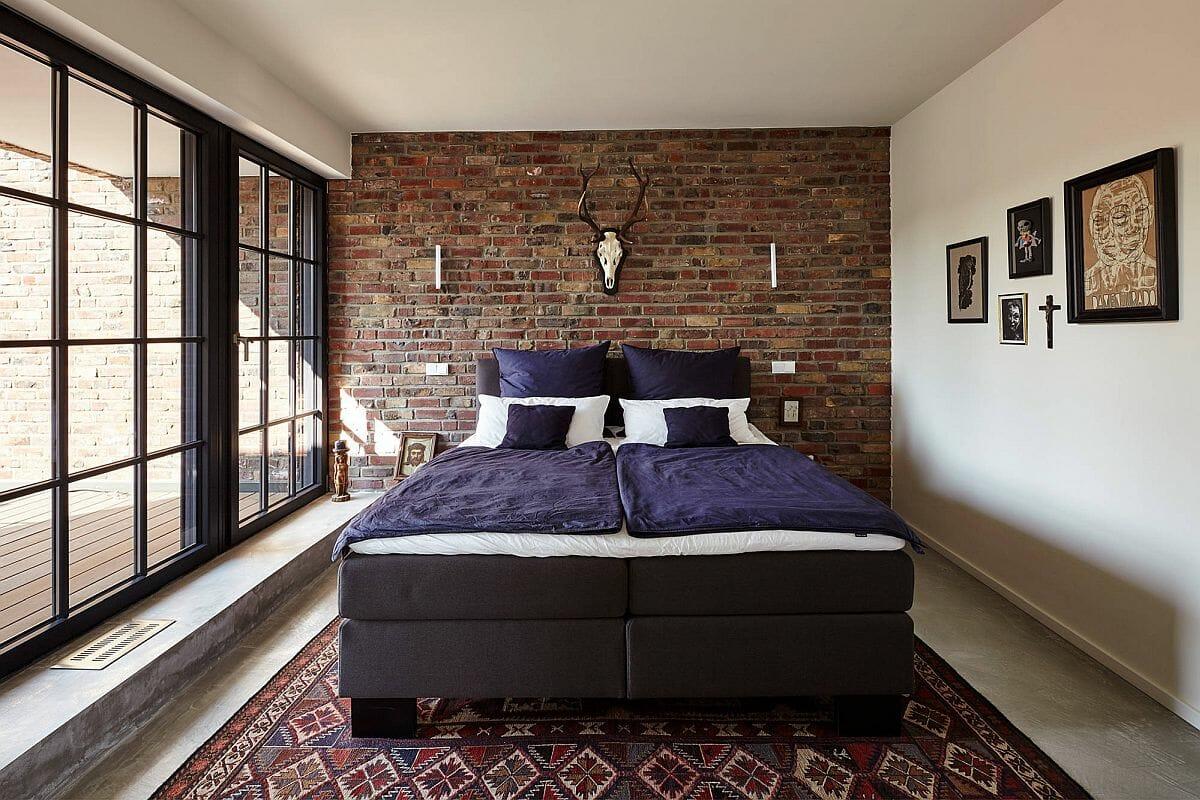 hình ảnh mẫu phòng ngủ phong cách công nghiệp hiện đại với tường gạch thô đầu giường, ga gối màu tím, thảm thổ cẩm