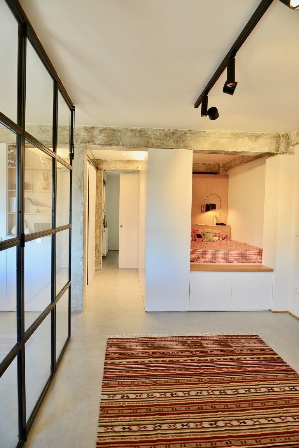 hình ảnh phòng ngủ nhỏ ấm cúng trong hốc tường với ga gối, chăn màu cam đất