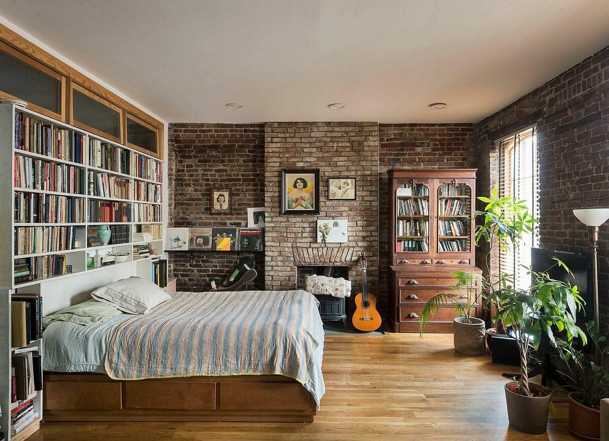 hình ảnh phòng ngủ với tường gạch nung đỏ, giá sách lớn đầu giường, cây xanh trang trí