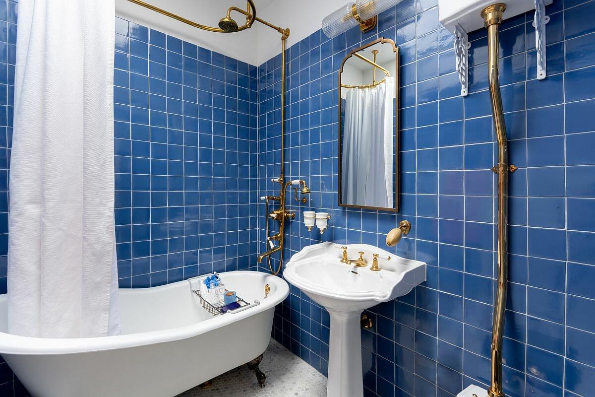 hình ảnh phòng tắm phong cách chiết trung ấn tượng với gạch ốp màu xanh dương, vòi sen kim loại mạ đồng sáng bóng