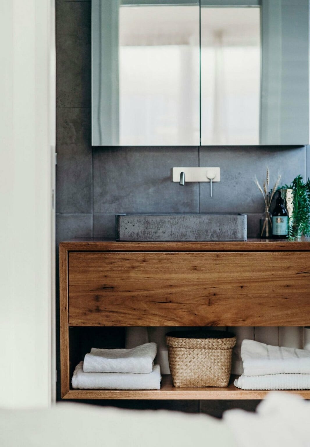 hình ảnh một góc phòng tắm mùa hè với tường bê tông xám sau gương soi, tủ gỗ mộc mạc