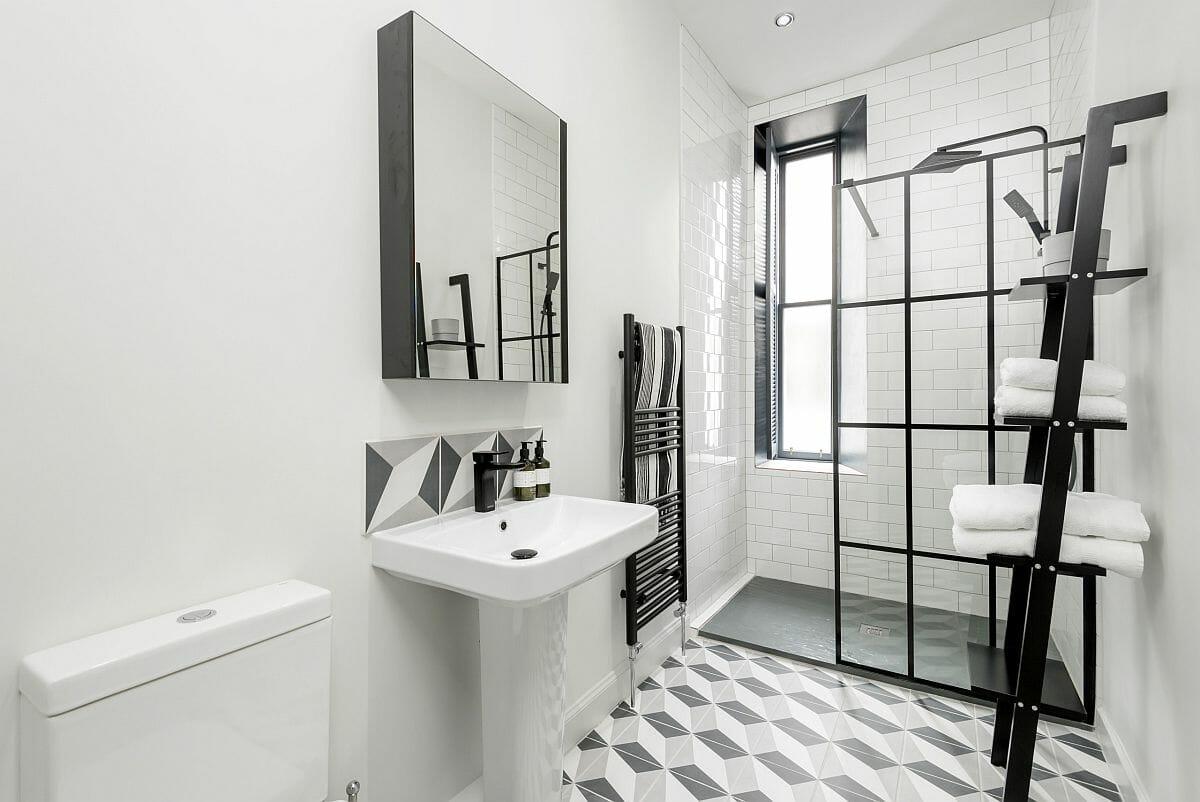 hình ảnh phòng tắm nhỏ với thang lưu trữ và khung cửa trượt kính màu đen bắt mắt