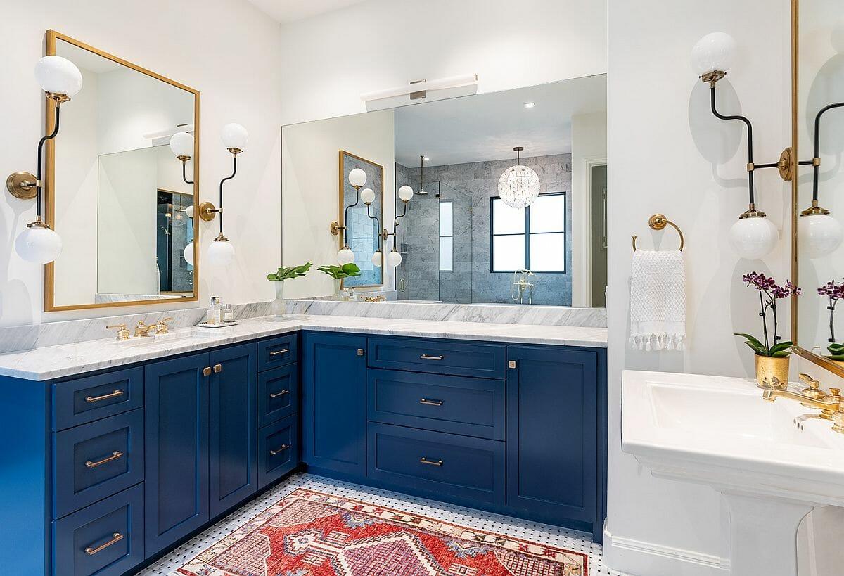 hình ảnh phòng tắm màu trắng chủ đạo, tủ màu xanh dương, khung gương, tay nắm ngăn kéo và chậu hoa mạ vàng sáng bóng