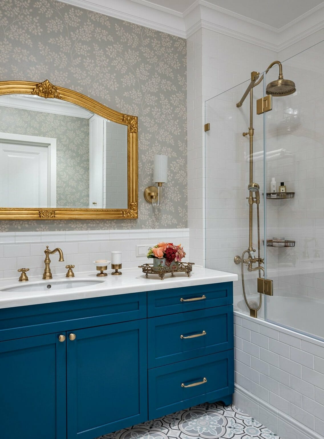 hình ảnh góc phòng tắm hiện đại, sang trọng với tủ màu xanh dương, khung gương mạ vàng, giấy dán tường họa tiết lá cây nhỏ