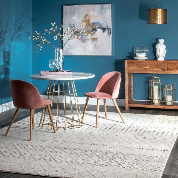 hình ảnh phòng ăn với tường sơn xanh dương, bàn ghế màu sắc, thảm trải màu trắng, tranh treo tường trừu tượng