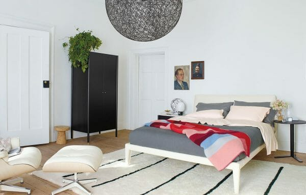 hình ảnh phòng ngủ tông màu trắng chủ đạo, sử dụng thảm trải sàn trắng kẻ sọc đen, chậu cây trang trí, đèn thả hình tròn xám lớn