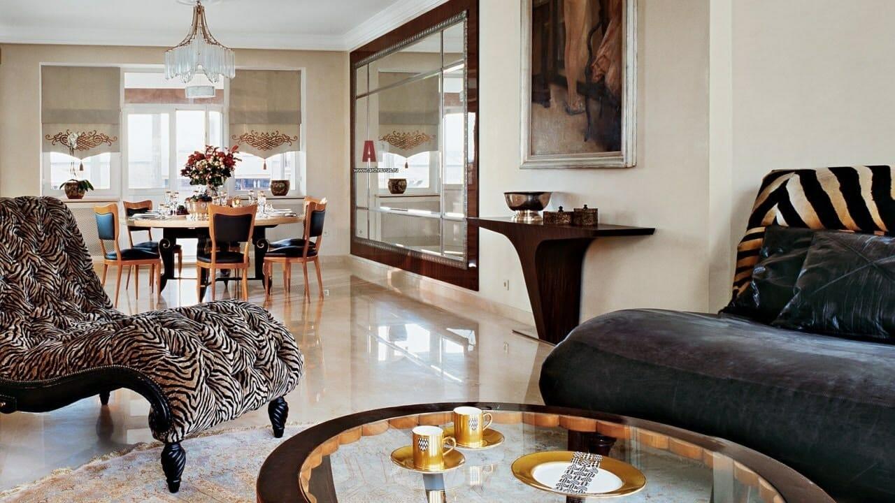 hình ảnh một góc phòng khách phong cách nội thất Art Deco với bàn trà tròn mặt kính, khung kim loại, sofa bọc nỉ, ghế thư giãn sang trọng, cạnh đó là bàn ăn