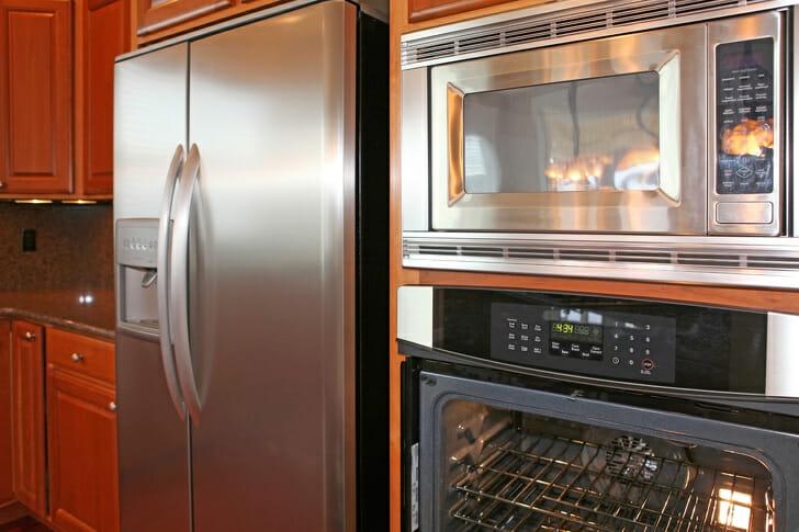 hình ảnh cận cảnh một góc phòng bếp với nhiều bề mặt kim loại từ tủ lạnh, lò nướng, bàn bếp