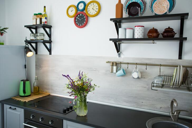 hình ảnh phòng bếp phong cách mộc mạc với kệ mở gắn tường, đồng hồ màu sắc, cây xanh trang trí