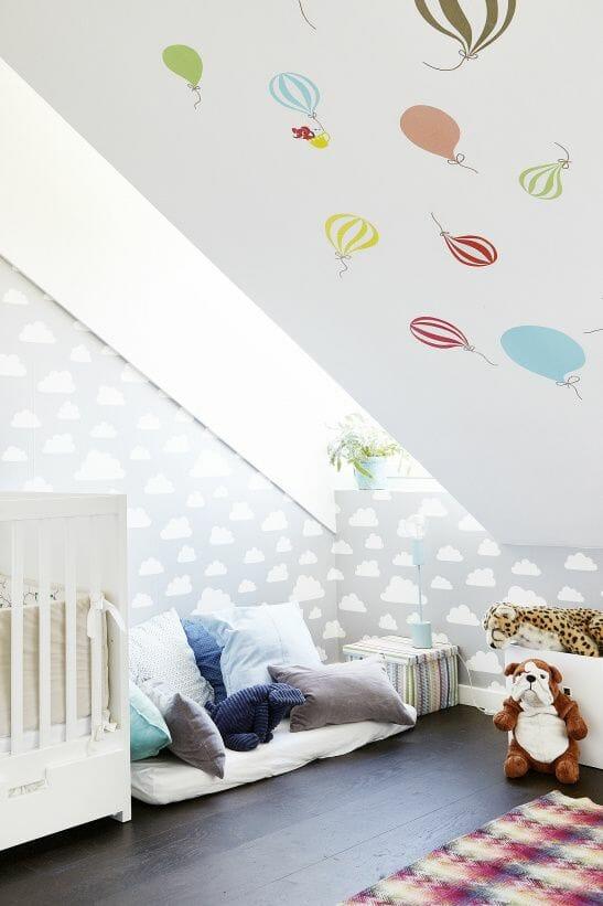 Phòng ngủ gác mái đáng yêu hơn bao giờ hết với những chiếc gối đầy màu sắc, một bức tường mây, trần nhà với những chiếc khinh khí cầu cho tâm hồn bay bổng và một số đồ chơi, món đồ nội thất họa tiết thổ cẩm