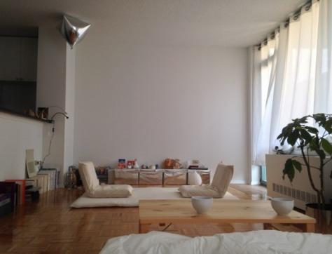 hình ảnh phòng sinh hoạt chung với thảm trải màu trắng, ghế ngồi bệt cùng tông, cạnh đó là bàn ăn