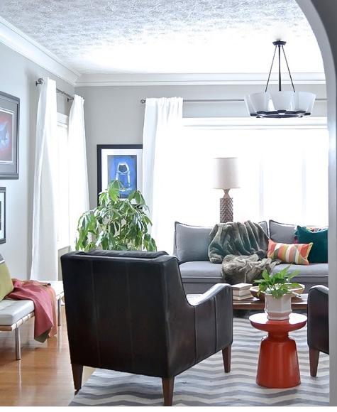 hình ảnh phòng khách phong cách hiện đại với sofa ghi xám, ghế bành màu đen, thảm trải kẻ sọc, rèm cửa sổ màu trắng