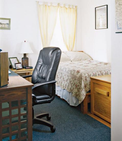 hình ảnh phòng ngủ nhỏ với cửa sổ đầu giường, bàn làm việc ngay cạnh, ghế da nặng nề
