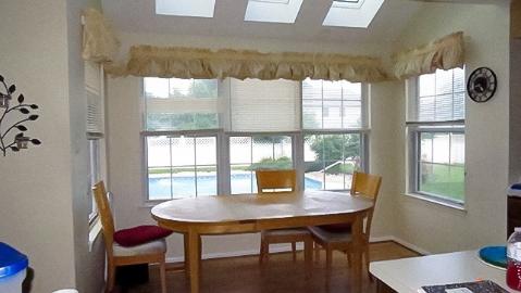 hình ảnh phòng ăn nhàm chán với bàn gỗ hình bầu dục, ghế ngồi đơn lẻ, rèm cửa lỗi thời