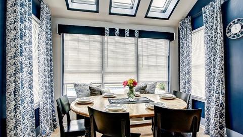 hình ảnh phòng ăn sang trọng với bàn tròn, ghế ngồi hợp mốt, rèm cửa họa tiết trắng, xanh dương kết hợp