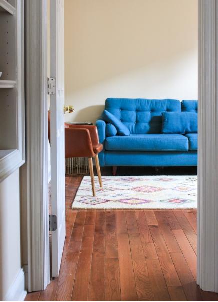 hình ảnh phòng khách với bức tường trống đơn điệu, sofa màu xanh da trời, ghế bành màu da bò ngay cạnh