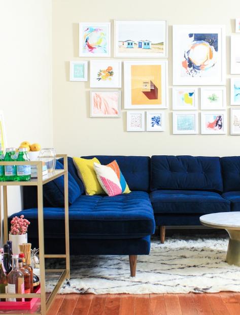 hình ảnh một góc phòng khách với sofa nhung xanh dương mềm mại, tranh treo tường, kệ gỗ lưu trữ ngay cạnh