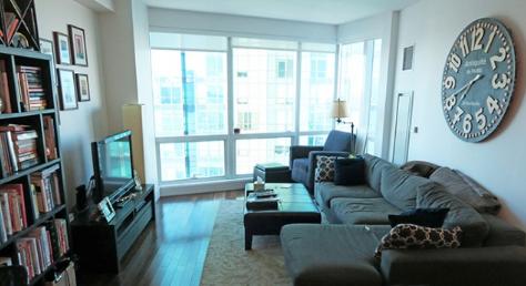 hình ảnh phòng khách nhỏ với sofa lớn màu xám đậm, tủ sách màu đen cao kịch trần.