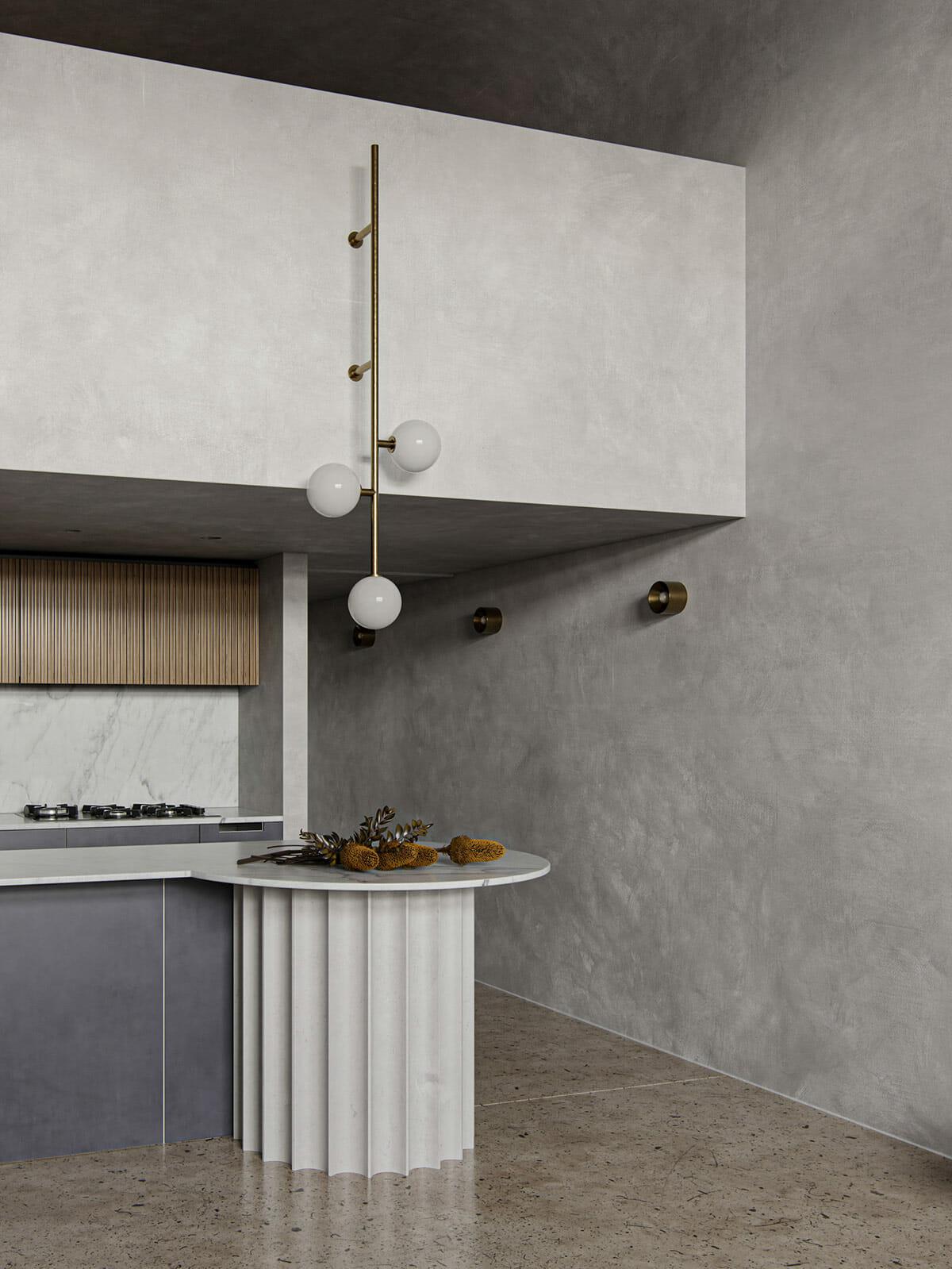 hình ảnh góp bếp trong căn hộ nhỏ với bàn đảo tròn màu ghi trắng, chân trụ góc cạnh độc đáo