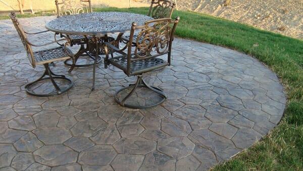 hình ảnh một góc sân vườn với bộ bàn ghế kim loại bắt mắt, sàn lát gạch bê tông giả đá