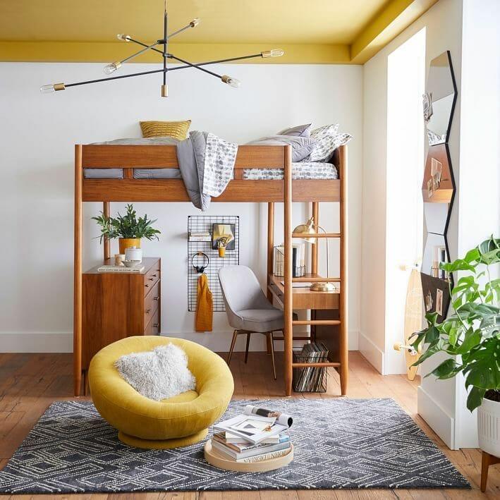 hình ảnh mẫu giường gác xép bằng gỗ tự nhiên, dưới đặt bàn học, tủ ngăn kéo, cạnh đó là ghế thư giãn màu vàng đặt trên thảm trải