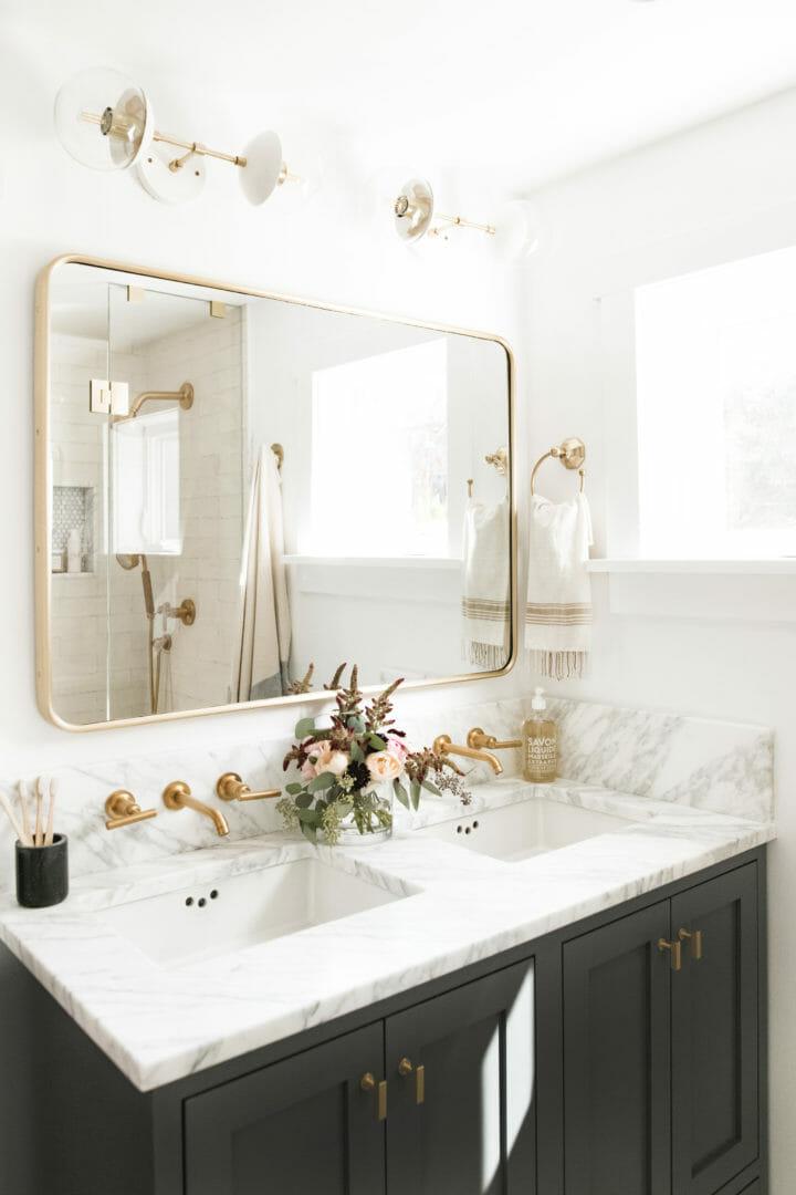 hình ảnh gương phòng tắm treo ở bức tường phía trên bồn rửa mặt, cạnh khung cửa sổ giúp hút sáng hiệu quả