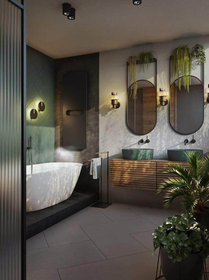 hình ảnh phòng tắm phong cách nhiệt đới với bồn tắm nắm đặt cạnh bức tường ốp gạch xanh, cạnh đó là bồn rửa mặt, phía trên treo gương hình bầu dục, cây xanh trang trí