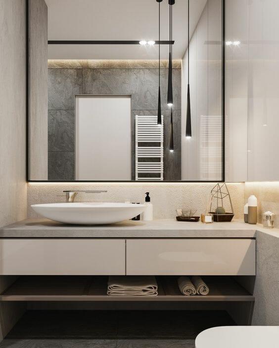hình ảnh một góc phòng tắm có thiết kế đơn giản, nổi bật với khung gương lớn treo trên bồn rửa mặt, phản chiếu bộ đèn thả trần hiện đại
