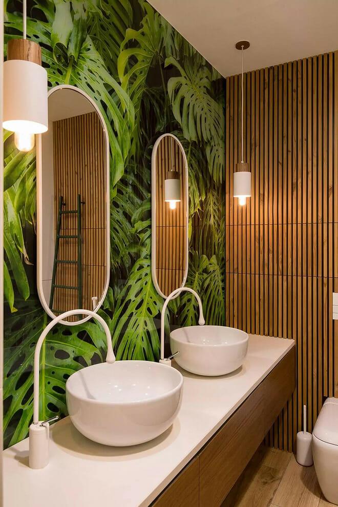 hình ảnh góc phòng tắm với bồn rửa đôi màu trắng, hai khung gương bầu dục treo tường, giấy dán tường họa tiết lá cây lớn