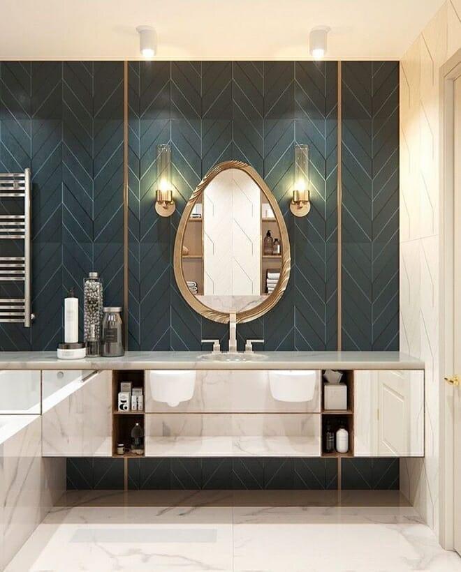 hình ảnh cận cảnh mẫu gương nhà tắm hình quả trứng với khung mạ vàng sáng bóng, nổi bật trên nền tường màu tối