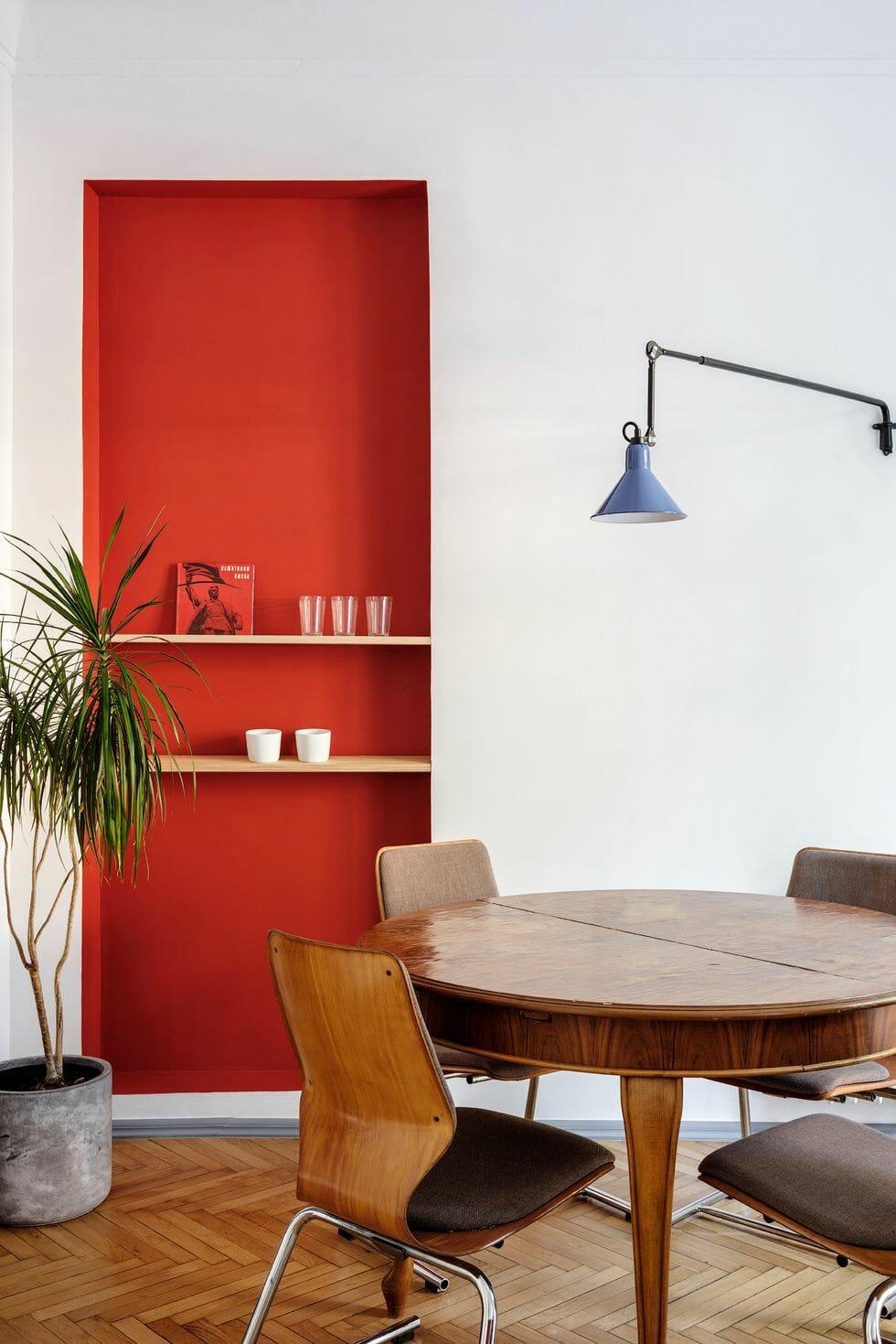 hình ảnh phòng ăn vói bàn tròn, bức tường màu đỏ cam, kệ nổi bằng gỗ