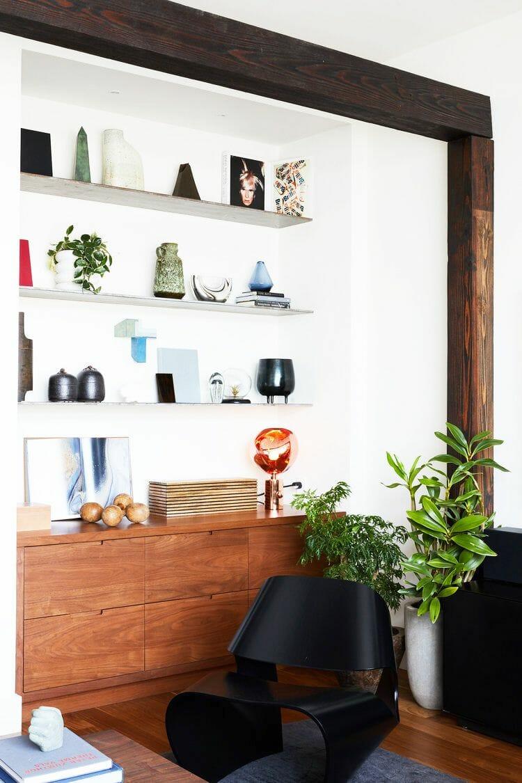 hình ảnh một góc phòng làm việc với bàn gỗ, ghế đen, kệ nổi gắn tường bày đồ trang trí