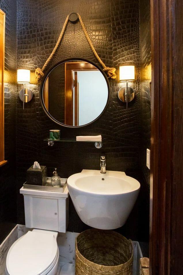 hình ảnh một góc phòng tắm ấn tượng với tường ốp gạch màu đen, gương tròn treo tường, kệ nổi bằng kính trong suốt