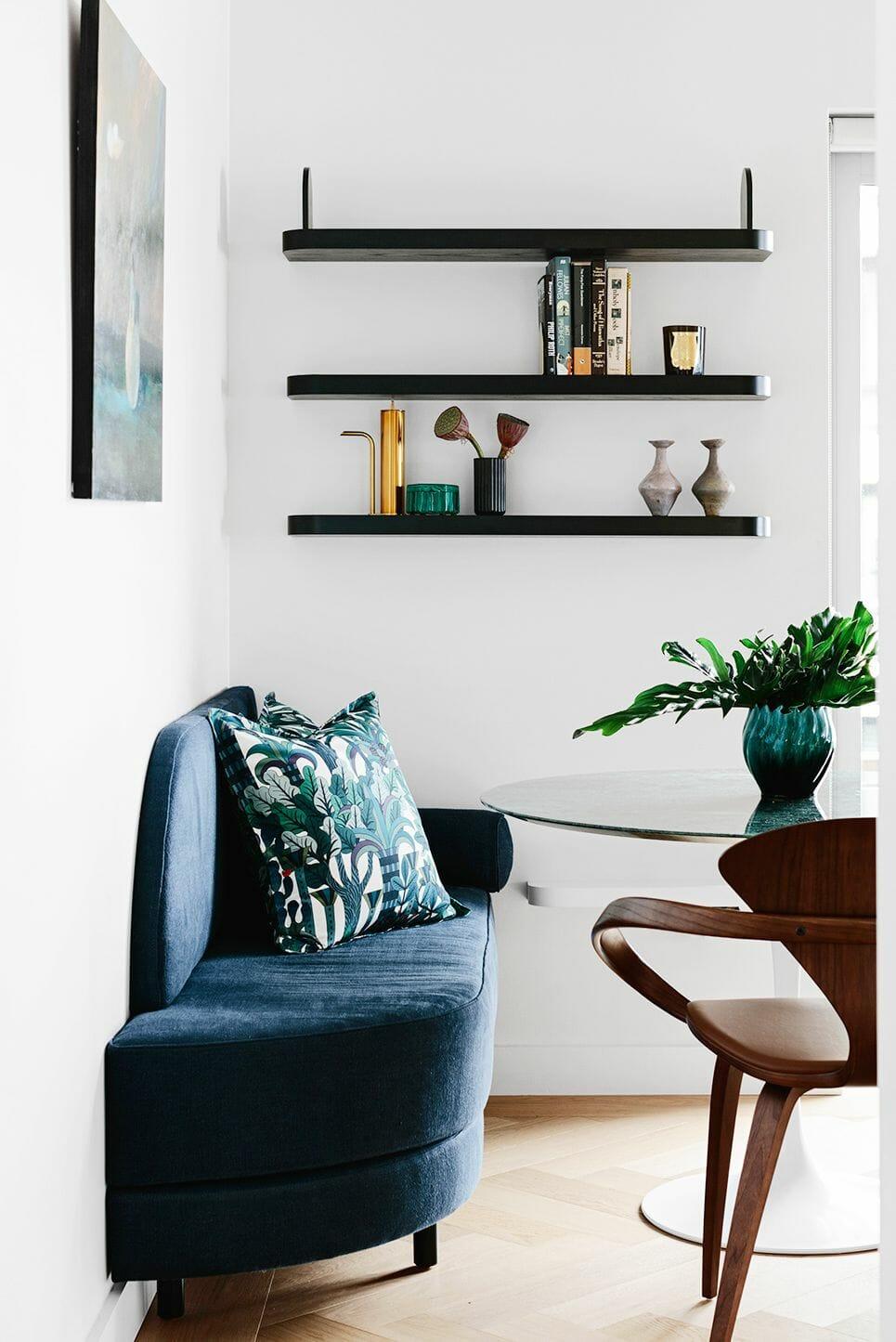 hình ảnh phòng ăn nhỏ đẹp với bàn tròn, ghế sofa bọc vải màu xanh dương, kệ gỗ màu đen nổi bật trên nền tường trắng